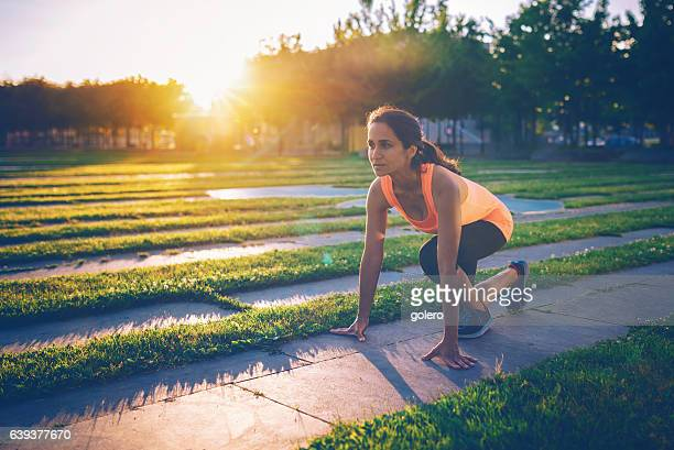 brazilian sportswoman preparing  for sprint outdoors in city at sundown