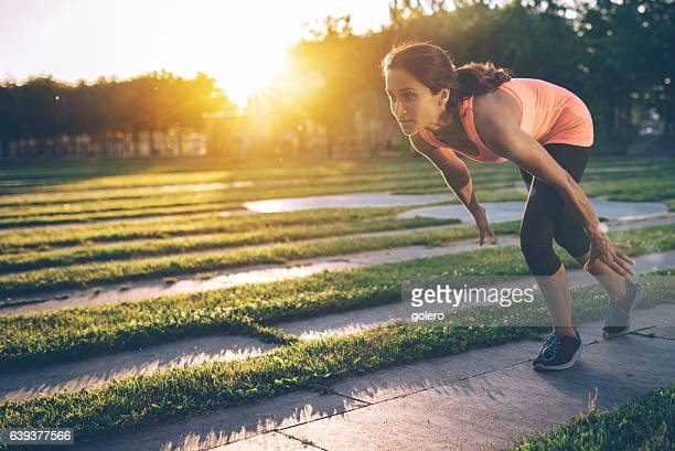 brazilian sportswoman starting for sprint outdoors in city at sundown