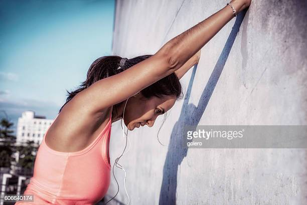 brazilian sportswoman stretching at concrete facade after running