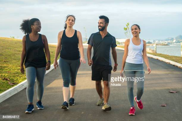 brazilian sporty friends walking on road against sky - walker stock photos and pictures