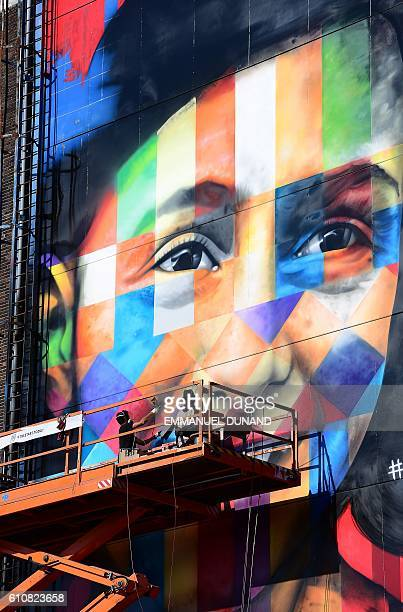 Brazilian street artist Eduardo Kobra and his assistant work on a large graffiti artwork of late writer Anne Frank at the shipyard at the NDSM...