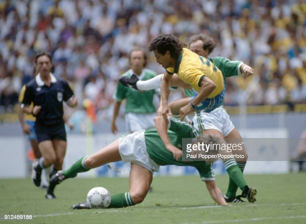 Brazilian striker Careca is upended by a tackle from Northern Ireland defender Alan McDonald during the FIFA World Cup match between Northern Ireland...
