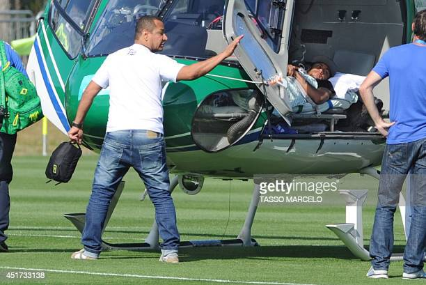 Brazilian striker Neymar lies on a strecher as his father Neymar da Silva Sr waves on July 5 2014 in the helicopter that will transport him from...