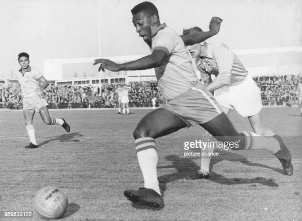 Brazilian striker Pele runs with the ball past a Swedish defender of the Malmoe FF soccer club during an international friendly between Malmoe FF and...