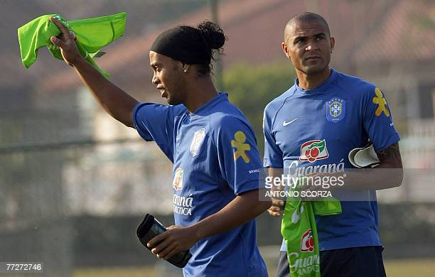 Brazilian striker Ronaldinho Gaucho waves a jersey as teammate Afonso Alves stands nearby 11 October 2007 at the Teresopolis training center some...