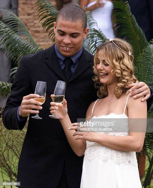 Brazilian striker Ronaldo and his bride Milene Dominques toast following their marriage 24 December 1999 in Rio de Janeiro. The 30-minute civil...