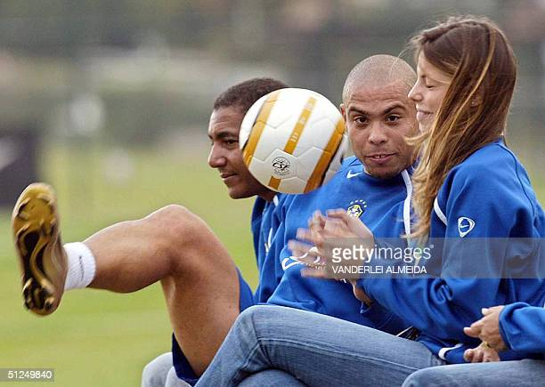 Brazilian striker Ronaldo Nazario fidgets with a ball and his girlfriend Brazilian model Daniele Cucarelli during a training session with the...