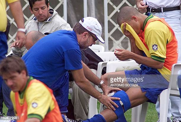 Brazilian striker Ronaldo wipes his face and receives an ice bag for his left knee during a training session at Chateau de Grande Romaine in Lesigny,...