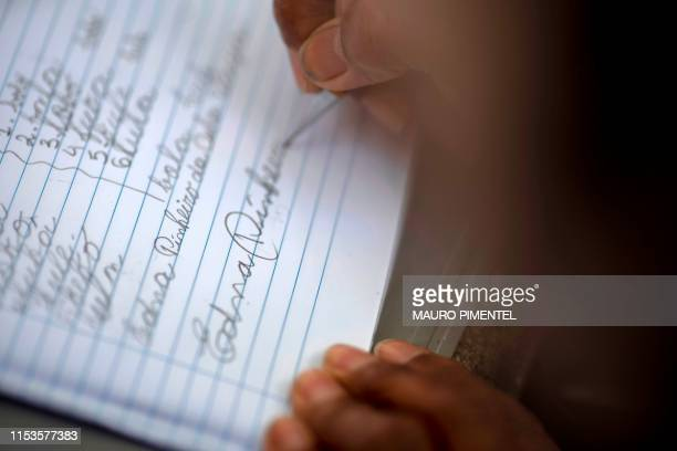 Brazilian student Edna Pinheiro writes her name during a Portuguese lesson as part of the project Aula na Praca at the Mauro Duarte Composer square...