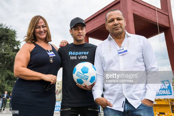 Brazilian superstar and world's most expensive footballer Neymar poses with his father Neymar Santos and his mother Nadine Santos next to a...
