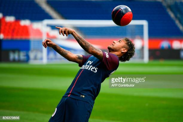 Brazilian superstar Neymar heads a ball during his official presentation at the Parc des Princes stadium on August 4 2017 in Paris after agreeing a...