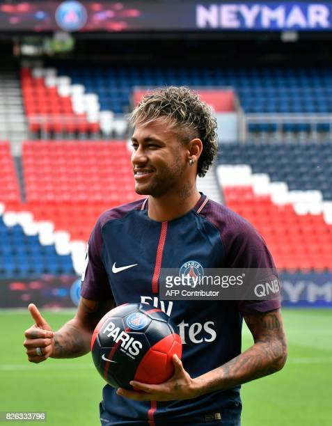 Brazilian superstar Neymar poses with a ball during his official presentation at the Parc des Princes stadium on August 4 2017 in Paris after...
