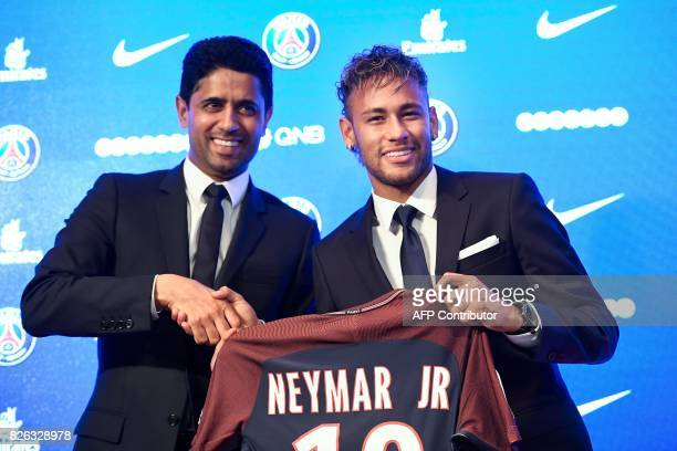 Brazilian superstar Neymar poses with his jersey next to Paris Saint Germain's Qatari president Nasser AlKhelaifi during a press conference at the...