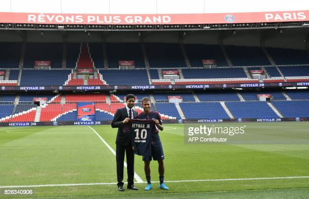 TOPSHOT Brazilian superstar Neymar poses with his jersey next to Paris Saint Germain's Qatari president Nasser AlKhelaifi during his official...