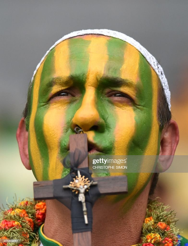 Brazilian supporter cheers for his team as he kisses a cross ahead of the semi-final football match between Brazil and Germany at The Mineirao Stadium in Belo Horizonte on July 8, 2014, during the 2014 FIFA World Cup.