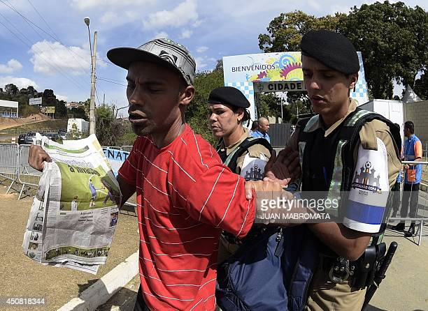 A Brazilian supporter of Argentina's forward Lionel Messi is arrested on June 18 2014 after he managed to enter the Cidade do Galo base camp of the...