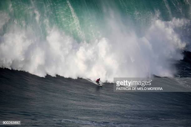 TOPSHOT Brazilian surfer Marcelo Luna rides a wave during the first surf session of 2018 at Praia do Norte in Nazare on January 1 2018 / AFP PHOTO /...