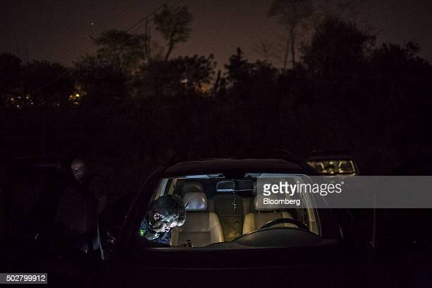 A Brazilian Tax Authority agent searches an abandoned armored car next to the Parana River near the border with Paraguay in Foz do Iguacu Brazil on...