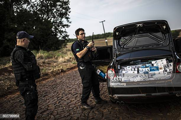 A Brazilian Tax Authority agent uses a radio to communicate to colleagues that he has discovered a load of smuggled cigarettes near the border with...