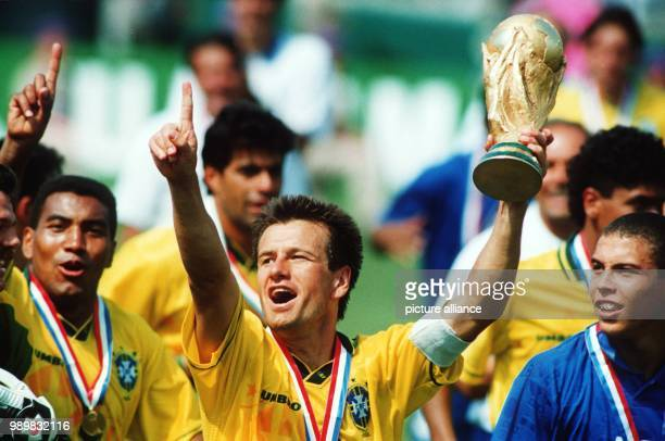 Brazilian team captain Dunga holds up the World Cup while he cheers and jubilates with his fellow teammates, among those midfielder Mauro Silva and...