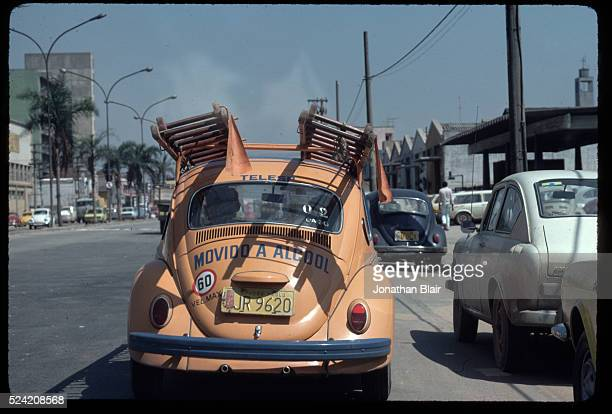 A Brazilian telephone company's fleet Volkswagen Beetle running on gasohol an alternative to gasoline made from sugarcane plants drives down a street...