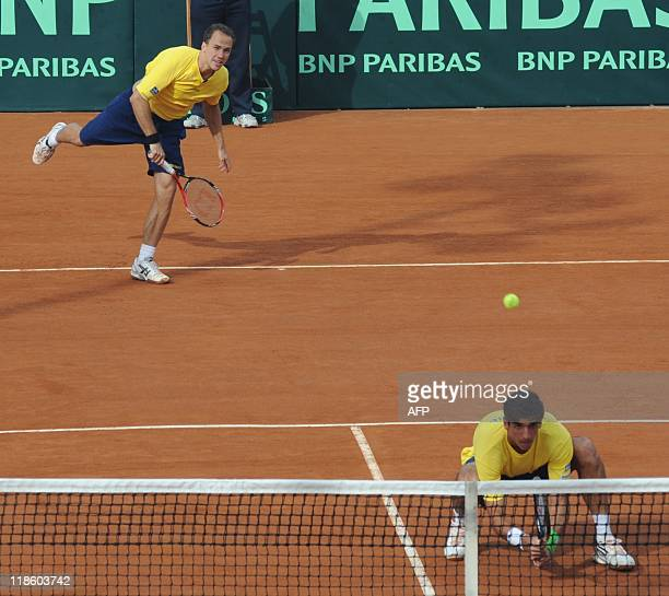 Brazilian tennis player Bruno Soares serves next to teammate Thomas Bellucci to the Uruguayan couple Martin Cuevas and Marcel Felder during their...
