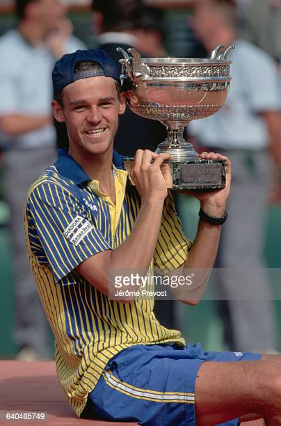 Brazilian tennis player Gustavo Kuerten holds the winner's trophy after his victory in the final match of the 1997 French Open.
