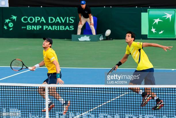 Brazilian tennis player Marcelo Demoliner and his teammate Marcelo Melo eye the ball during their Americas Zone Group I 2nd round Davis Cup tennis...