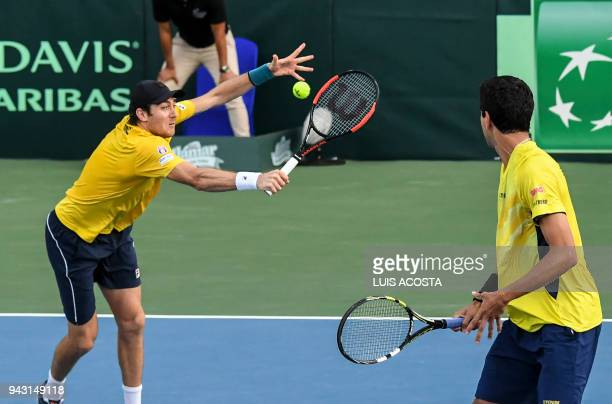 Brazilian tennis player Marcelo Demoliner returns a ball next to his teammate Marcelo Melo against Colombian tennis players Juan Sebastian Cabal and...
