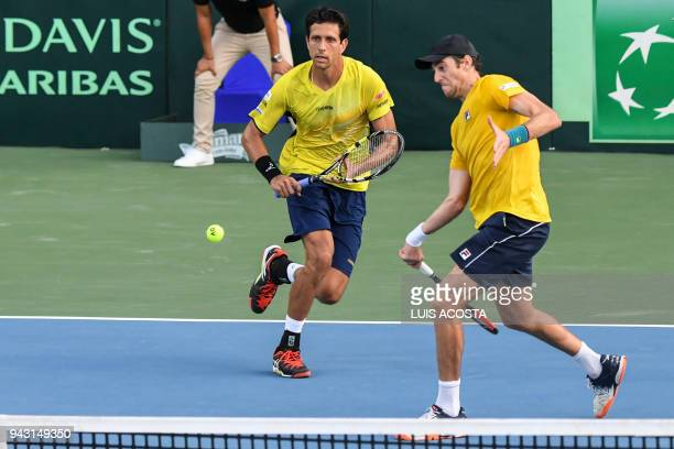 Brazilian tennis player Marcelo Demoliner returns a ball nexto to his teammate Marcelo Melo against Colombian tennis players Juan Sebastian Cabal and...