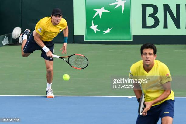 Brazilian tennis player Marcelo Demoliner serves next to his teammate Marcelo Melo against Colombian tennis players Juan Sebastian Cabal and Robert...