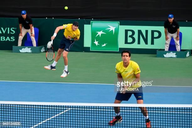 Brazilian tennis player Marcelo Demoliner serves next to teammate Marcelo Melo against Colombian tennis players Juan Sebastian Cabal and Robert Farah...