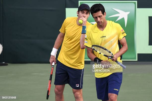 Brazilian tennis player Marcelo Demoliner speaks with his teammate Marcelo Melo during their Americas Zone Group I 2nd round Davis Cup tennis doubles...