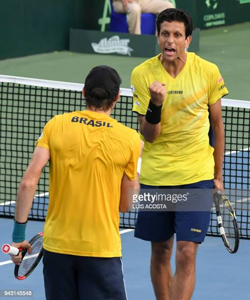 Brazilian tennis player Marcelo Melo celebrates with his teammate Marcelo Demoliner after winning a point against Colombian tennis players Juan...