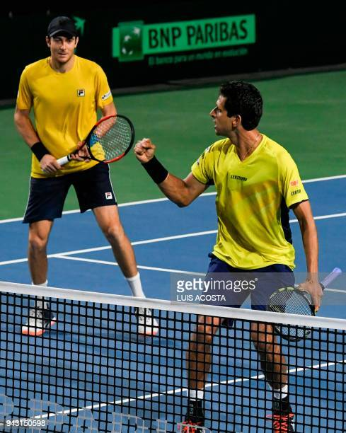 Brazilian tennis player Marcelo Melo celebrates with his teammate Marcelo Demoliner after defeating Colombian tennis players Juan Sebastian Cabal and...