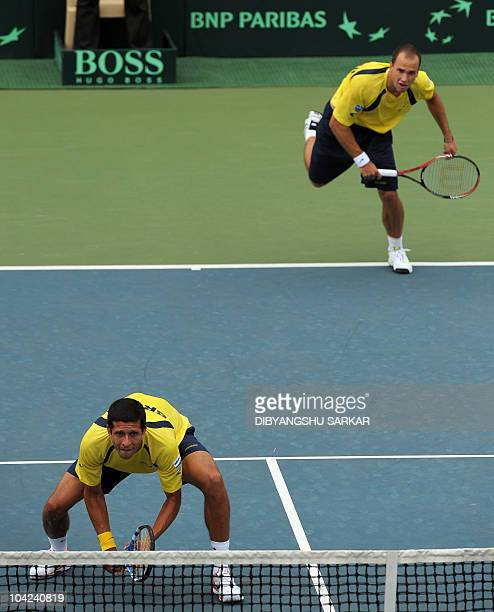 Brazilian tennis player Marcelo Melo eyes the ball as teammate Bruno Soares serves during their doubles match against Indian pair of Mahesh Bhupathi...