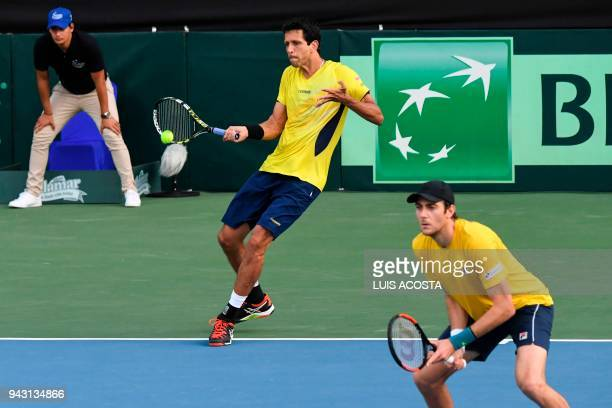 Brazilian tennis player Marcelo Melo returns a ball next to teammate Marcelo Demoliner against Colombian tennis players Juan Sebastian Cabal and...