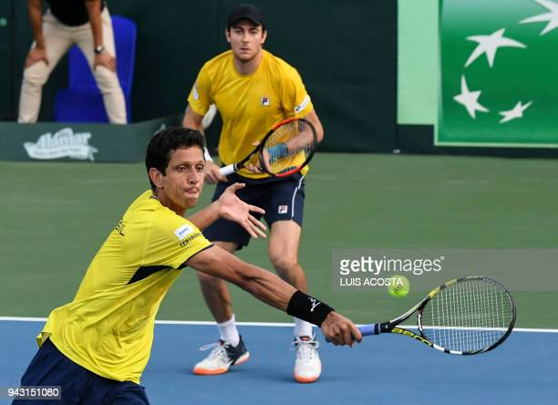 Brazilian tennis player Marcelo Melo returns a ball to Colombian tennis players Juan Sebastian Cabal and Robert Farah as teammate Marcelo Demoliner...