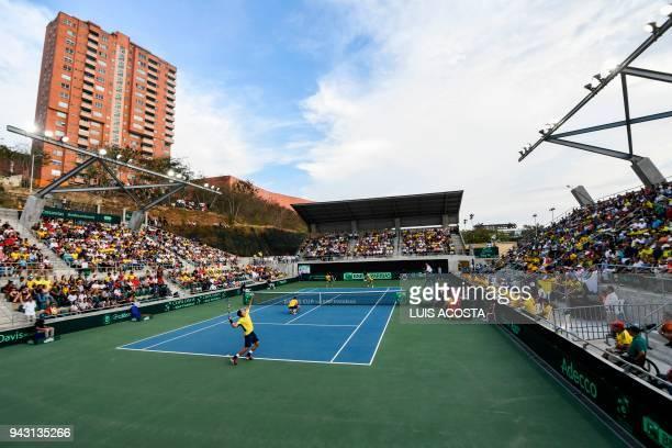 Brazilian tennis player Marcelo Melo serves as teammate Marcelo Demoliner bends against Colombian tennis players Juan Sebastian Cabal and Robert...