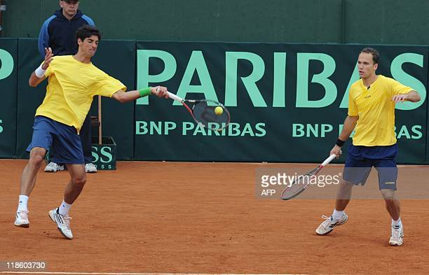Brazilian tennis player Thomas Bellucci hits the ball next to teammate Bruno Soares to Uruguayans Martin Cuevas and Marcel Felder during their Davis...