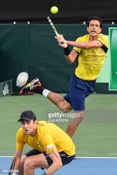 Brazilian tennis players Marcelo Melo returns a ball as teammate Marcelo Demoliner bends against Colombian tennis player Juan Sebastian Cabal and...