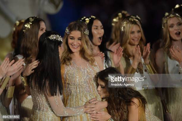 Brazilian top models Adriana Lima is seen as Isabeli Fontana kisses the belly of pregnant Brazilian model Ana Beatriz Barros at the runway during the...