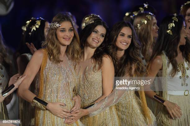 Brazilian top models Isabeli Fontana Izabel Goulart and pregnant top model Ana Beatriz Barros salute the people at the runway during the Dosso Dossi...