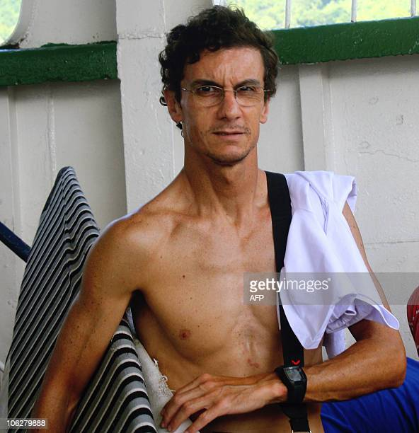 Brazilian tourist Fabio Junquieira Karkow who survived the tsunami on Indonesia's Mentawai island arrives carrying a surfboard on a commercial ferry...