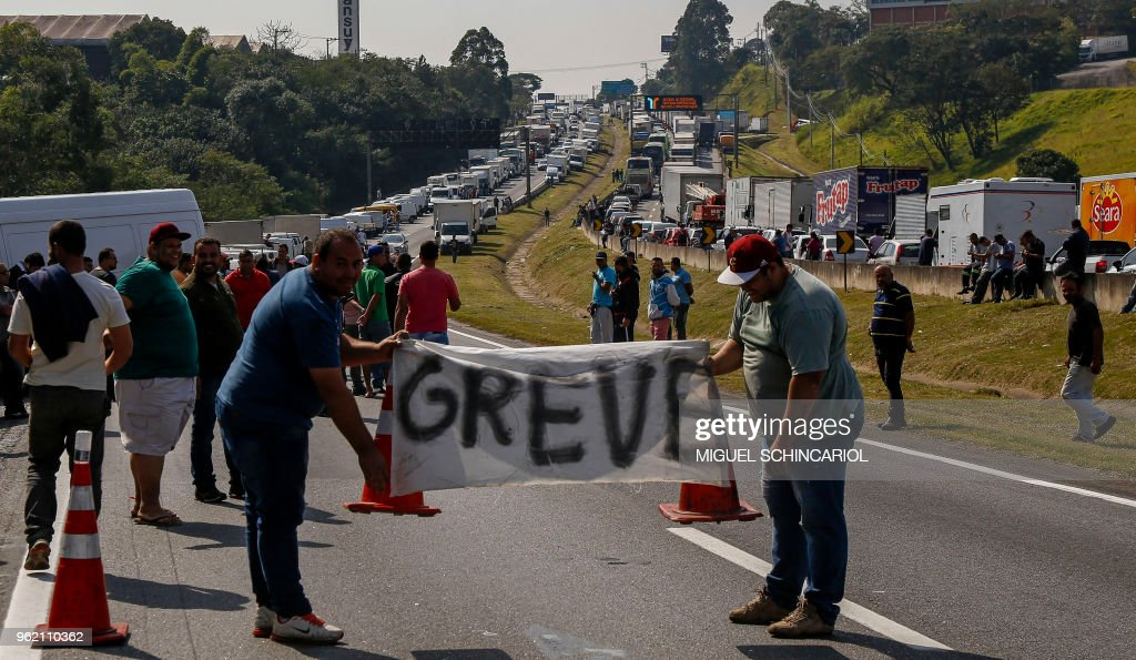 Brazilian truck drivers hold a banner reading 'strike' as they block the Regis Bittencourt road, 30 kilometres from Sao Paulo, during the fourth day of strike to protest rising fuel costs in Brazil, on May 24, 2018.