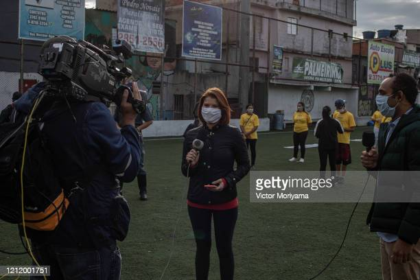 Brazilian TV team broadcasts live first aid training promoted by firefighters to residents of the Paraisopolis neighborhood on May 6 2020 in Sao...