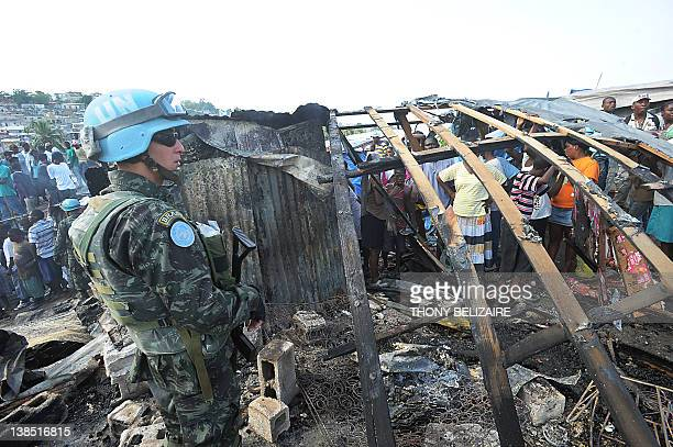 A Brazilian UN peacekeeper surveys damage as Haitians search through the rubble after a fire swept through a tent city February 8 2012 in the center...
