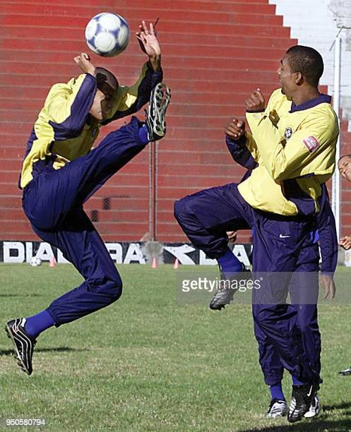 Brazilian Under20 player Adriano jumps to fight for the ball with his teammate Robert 26 June 2001 during their training session in Cordoba Argentina...