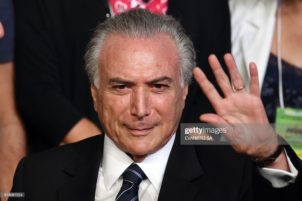 Brazilian Vice President Michel Temer waves during the Brazilian Democratic Movement Party (PMDB) national convention in Brasilia, on March 12, 2016. The PMDB convention will discuss if they continue supporting the government or if they will back the impeachment of President Dilma Rousseff in Congress.