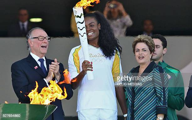 Brazilian volleyball player Fabiana Claudino holds the Olympic torch as Brazilian President Dilma Rousseff and Brazilian Olympic Committee President...